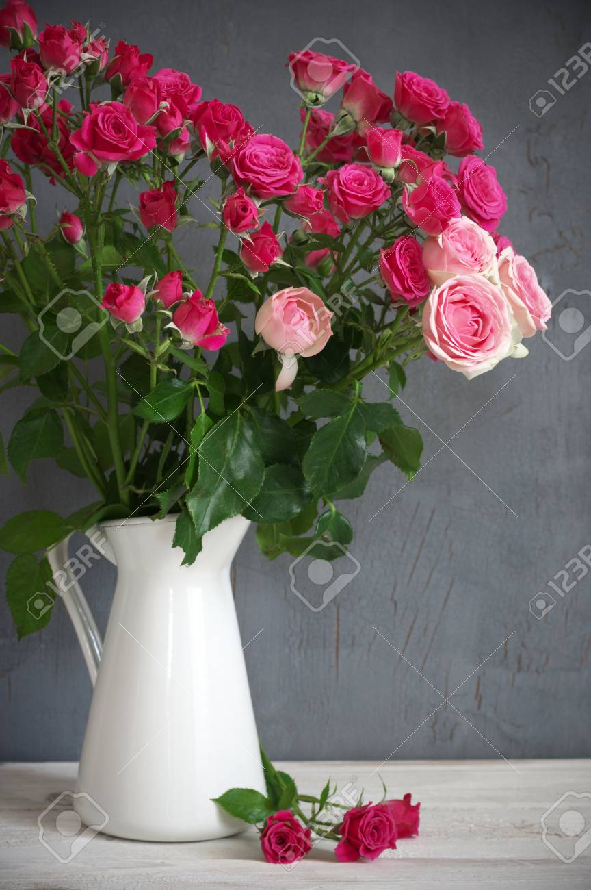 Bouquet Of Crimson And Pink Spray Roses In Jug On White Wooden