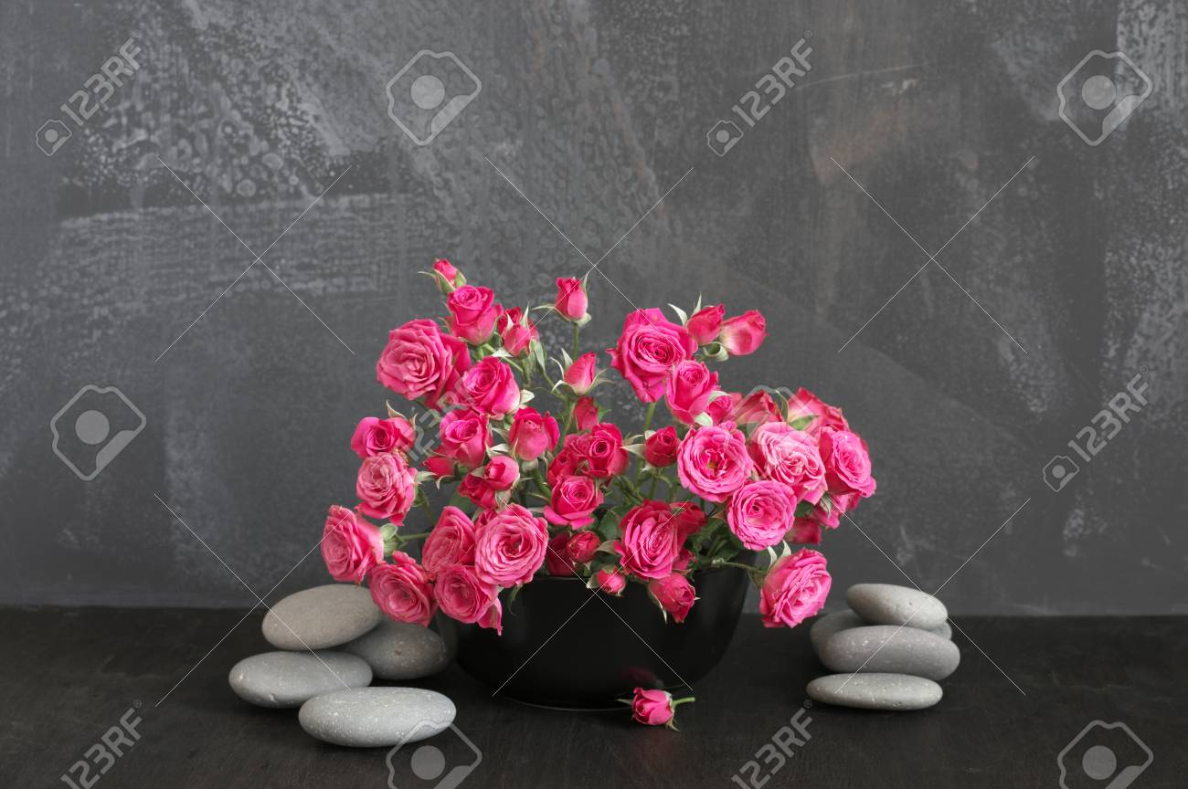Bouquet of crimson spray roses in black vase and pebble on black..