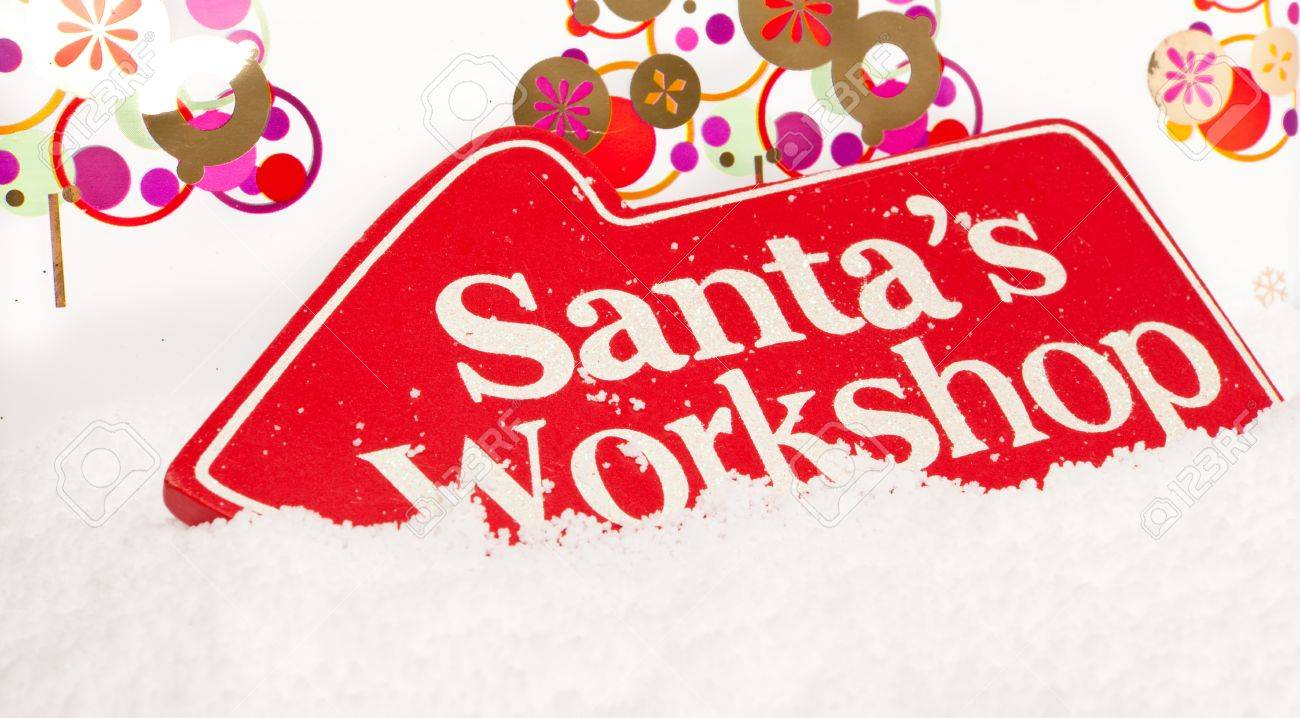A red sign showing the way to santas workshop sat in snow Stock Photo - 10865533