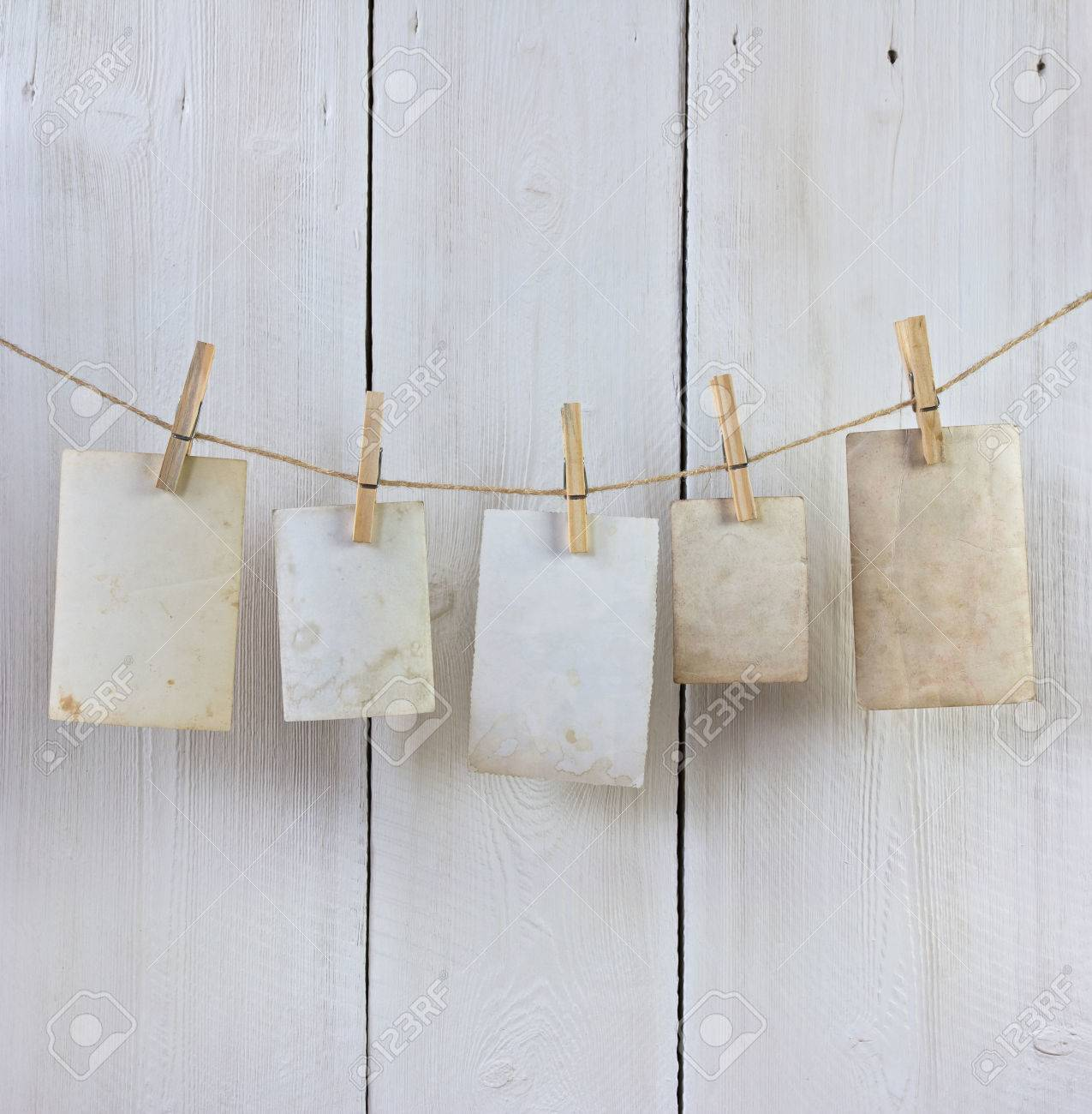 old photos hanging on the rope with a clothespin against white planks - 41921441