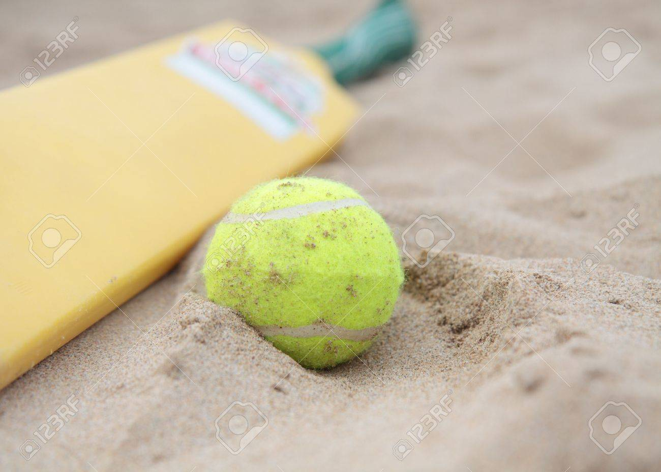 A Beach Cricket Bat With Tennis Ball On The Sand Stock Photo