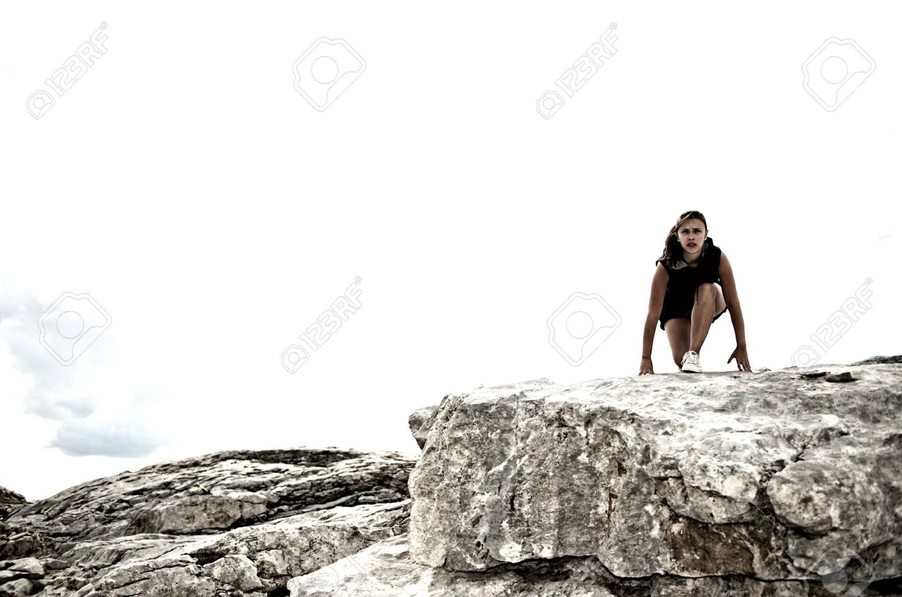 Athletic woman on a rock starting to run Stock Photo - 5525928