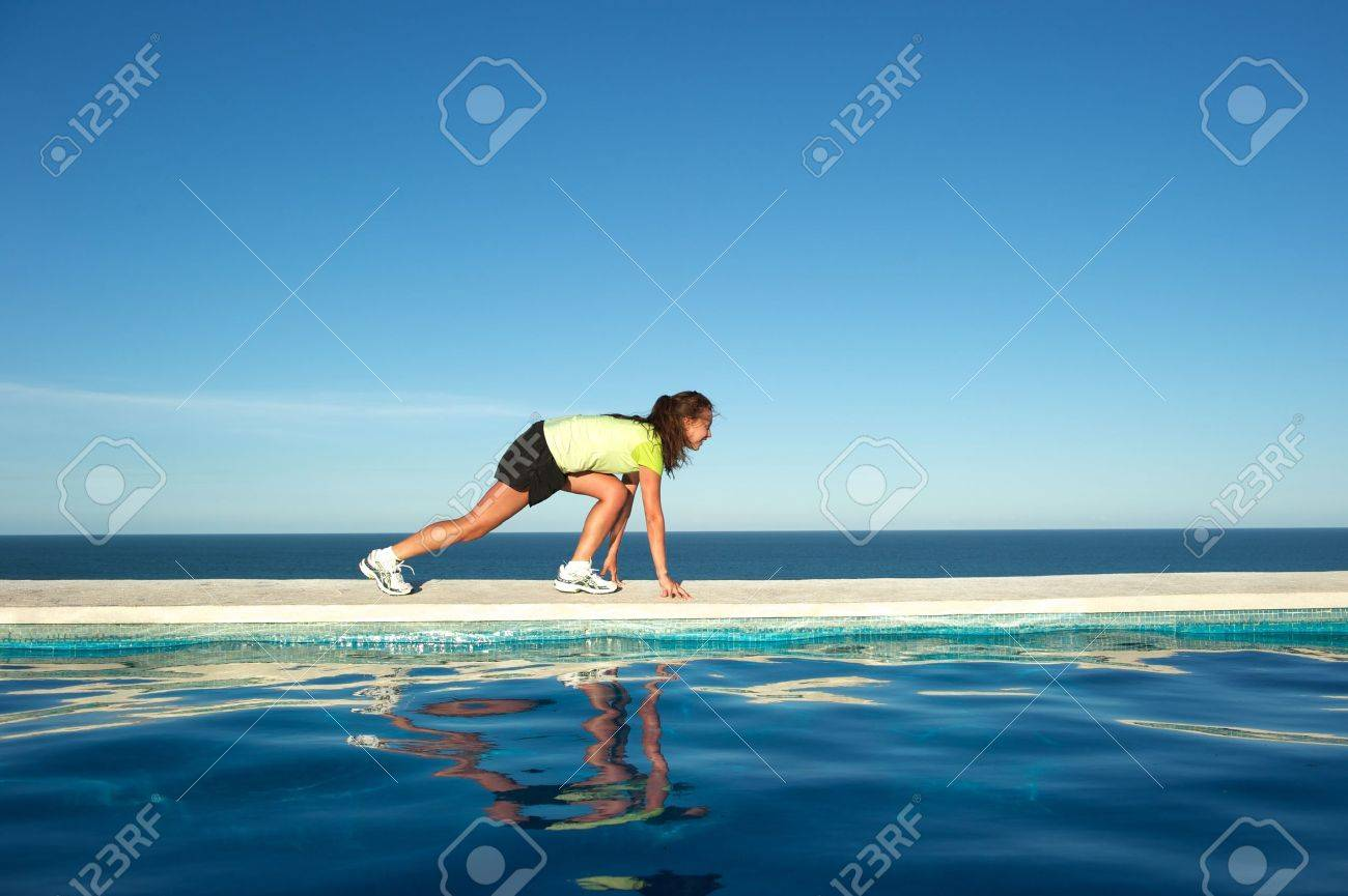 Woman doing exercises on the wall of a swimming pool with sea view in Arraial d'Ajuda, Bahia State, Brazil Stock Photo - 7219661
