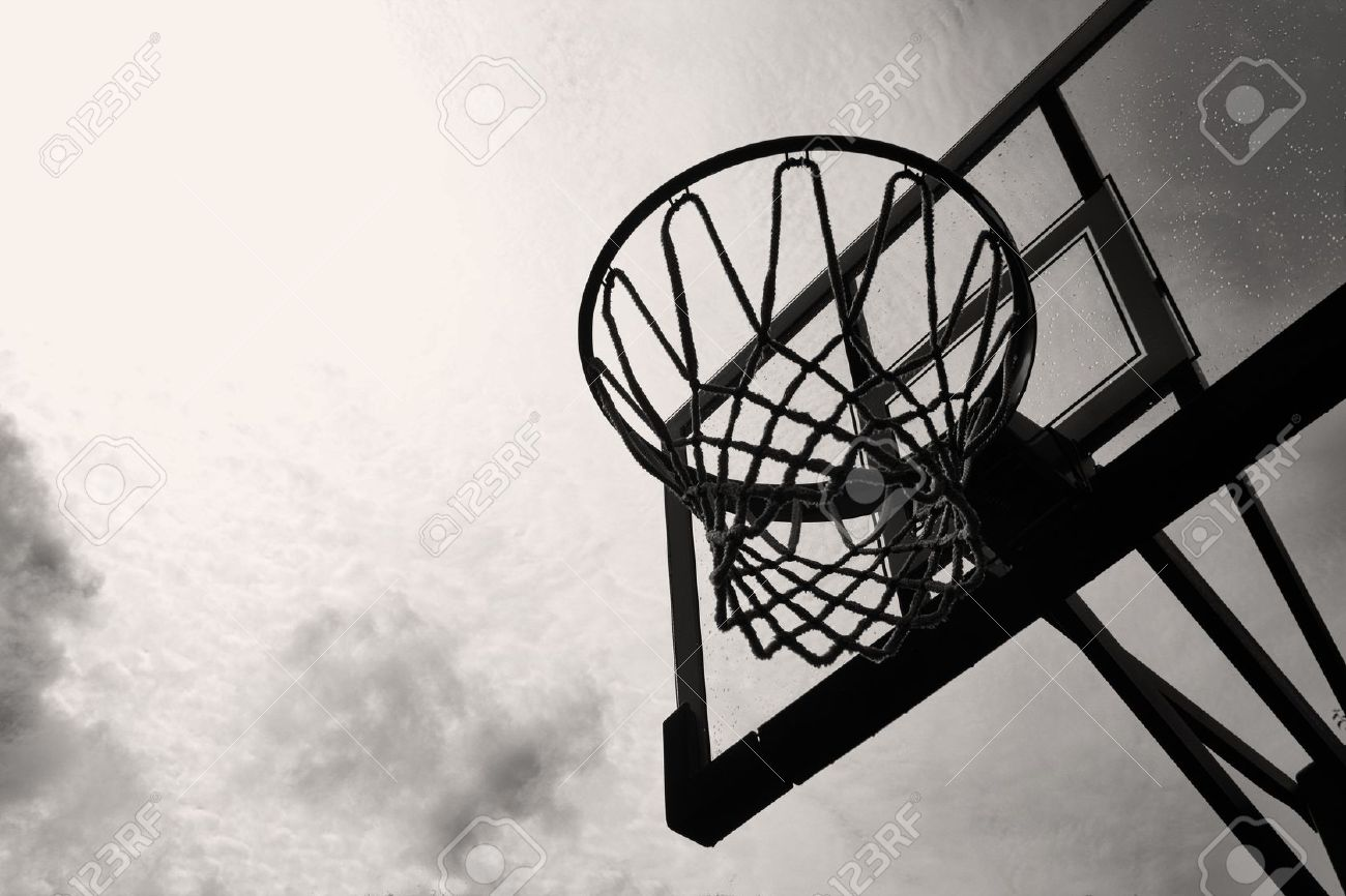 A basketball hoop and backboard against a stormy sky in black and white stock photo