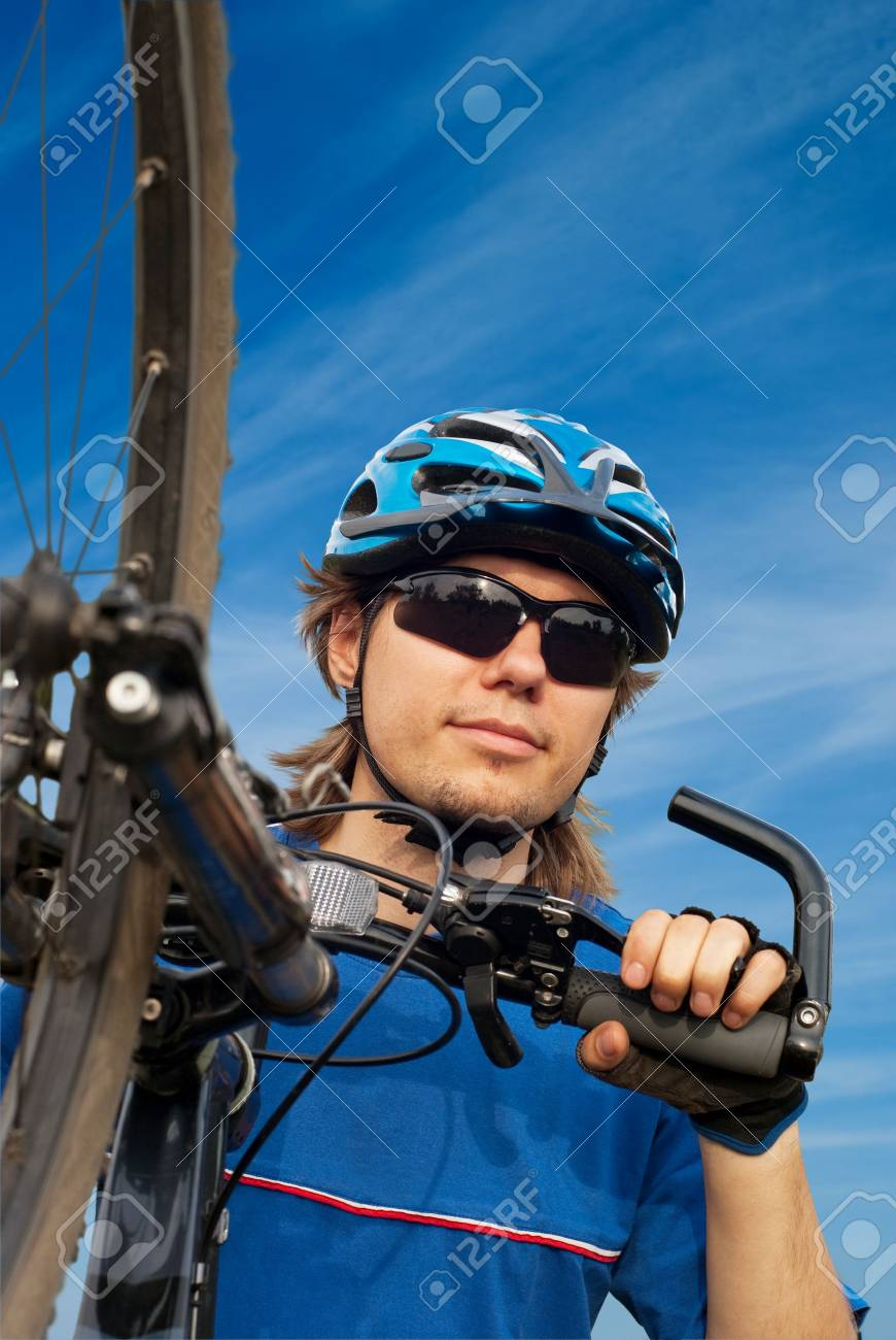 portrait of a young bicyclist in helmet with bicycle in the foreground - 6080541