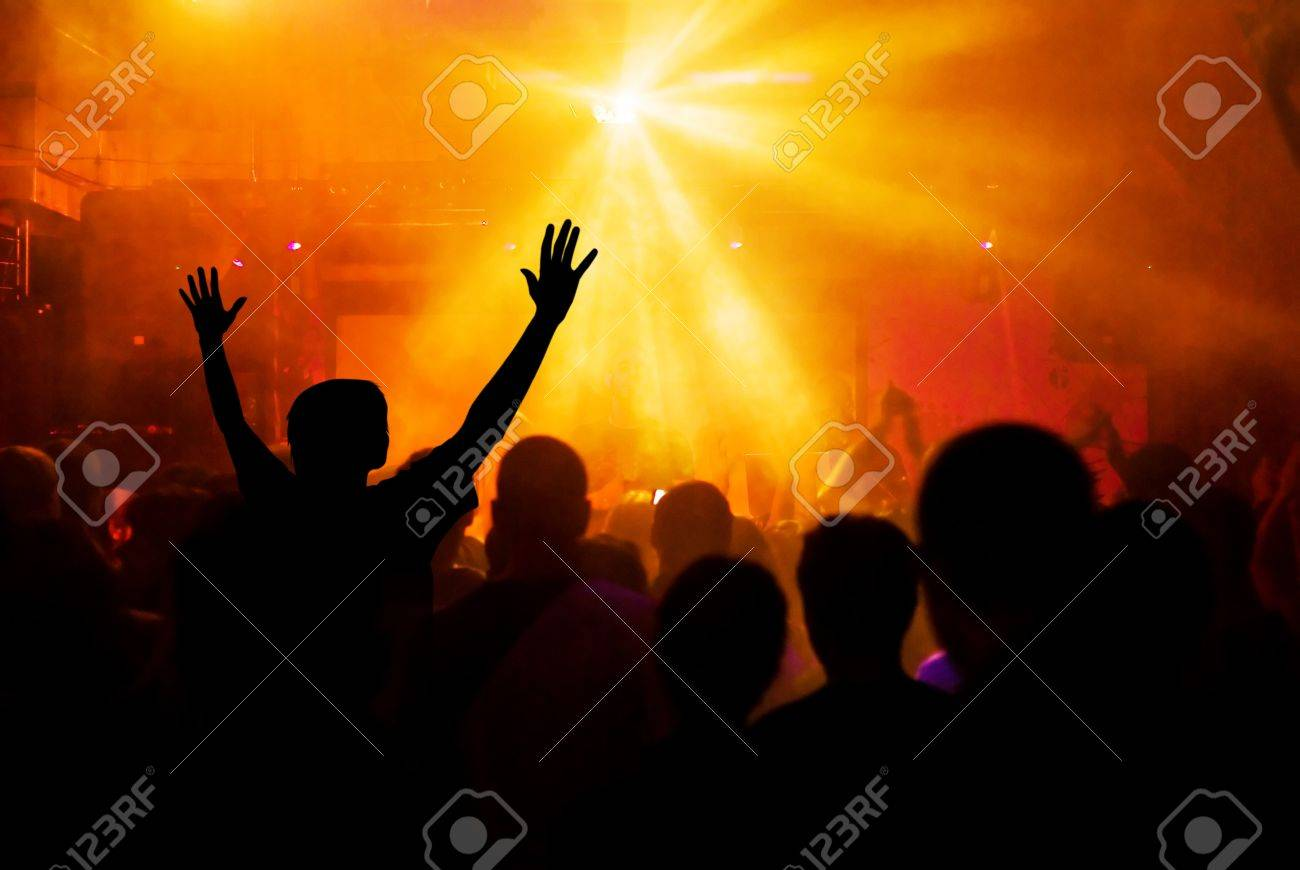 photo of hands at rock concert, silhouettes against stage lighting - 7800070