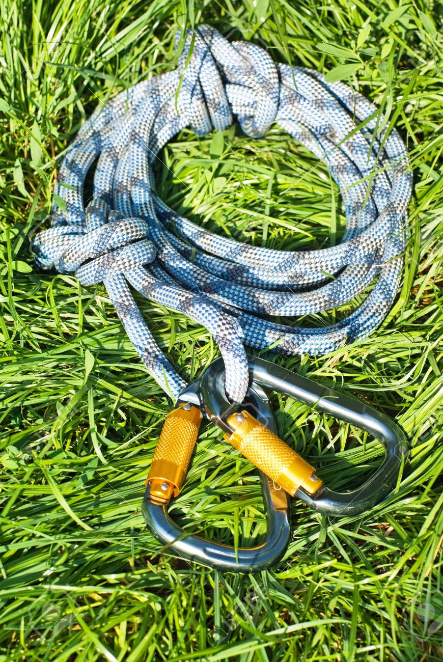climbing equipment - carabiners and rope on the grass - 7924360