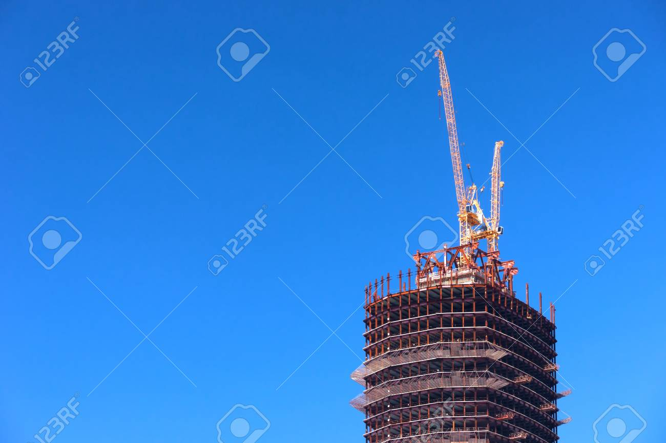Construction. Two cranes on the top of the tower - 9344600