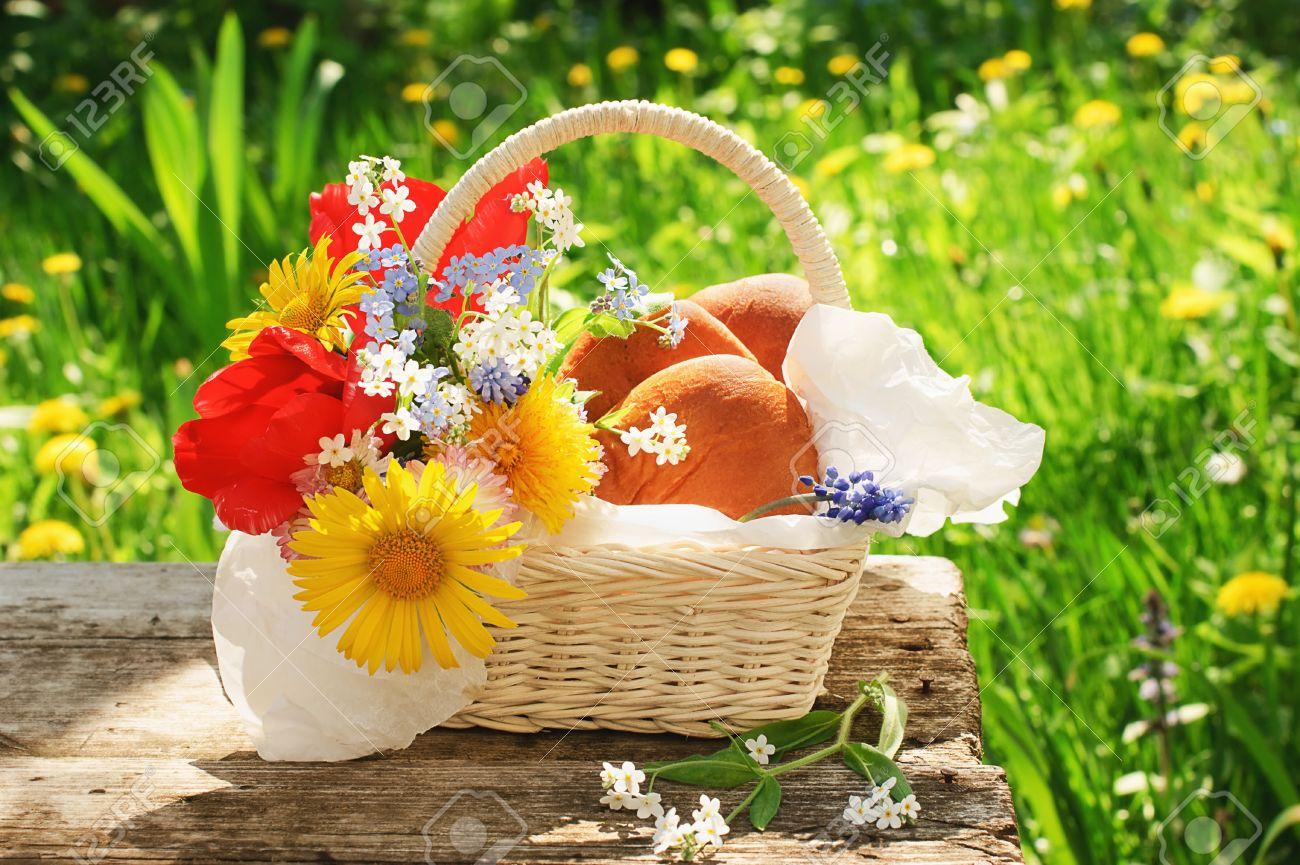 Panier blanc avec pâtés et de fleurs lumineuses sur l\'ancienne table dans  le jardin à la belle journée d\'été