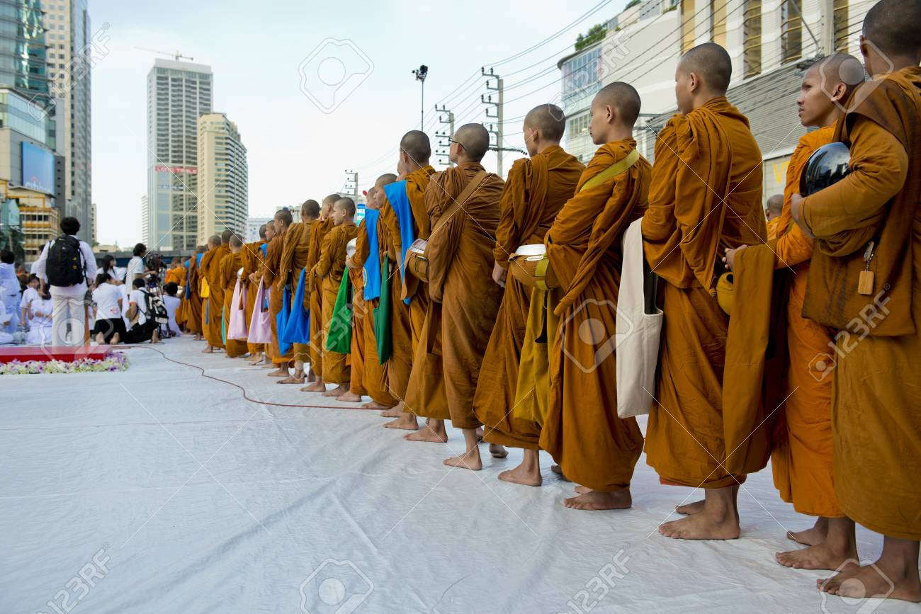 Bangkok, Thailand � July 7, 2012: Alms giving-ceremony - Thousands of monks celebrate the enlightenment of Siddhartha Gautama, which dates back 2600 years ago Stock Photo - 14418466