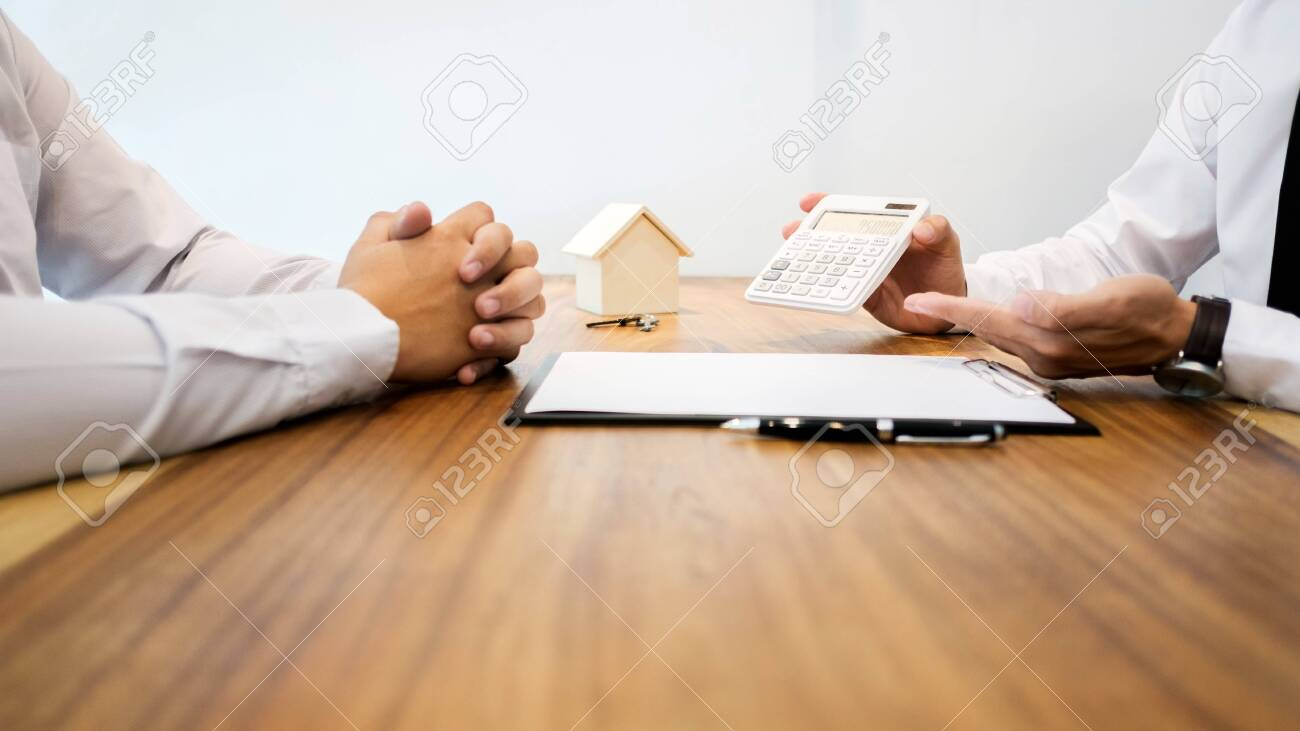 Real Estate agent showing a contract signature with customer to making a valuation deal - 127566209