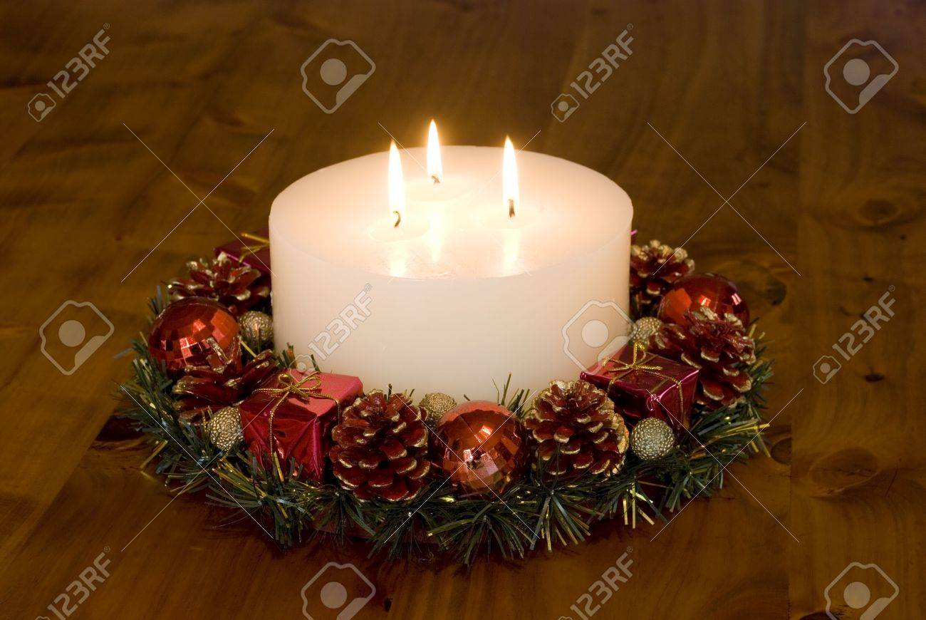 a 3 wick christmas candle in a wreath stock photo picture and