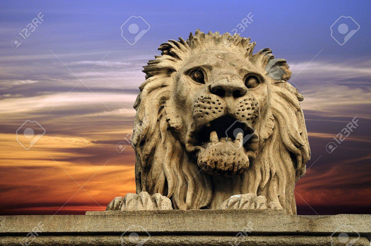 Lion statue from Budapest bridge on bright sky - 7563518
