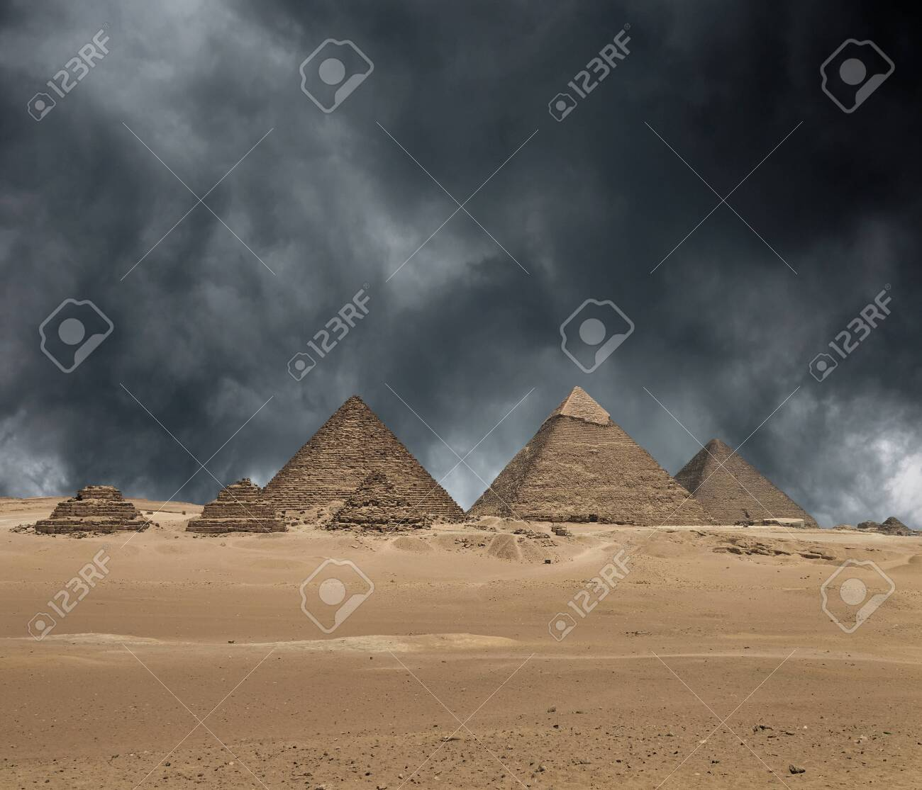 The Giza pyramid complex, or the Giza Necropolis on the Giza Plateau in Egypt near Cairo includes the Great Pyramid of Giza the Pyramid of Khafre and the Pyramid of Menkaure under dramatic grey stormy sky. Composite image. - 142812703