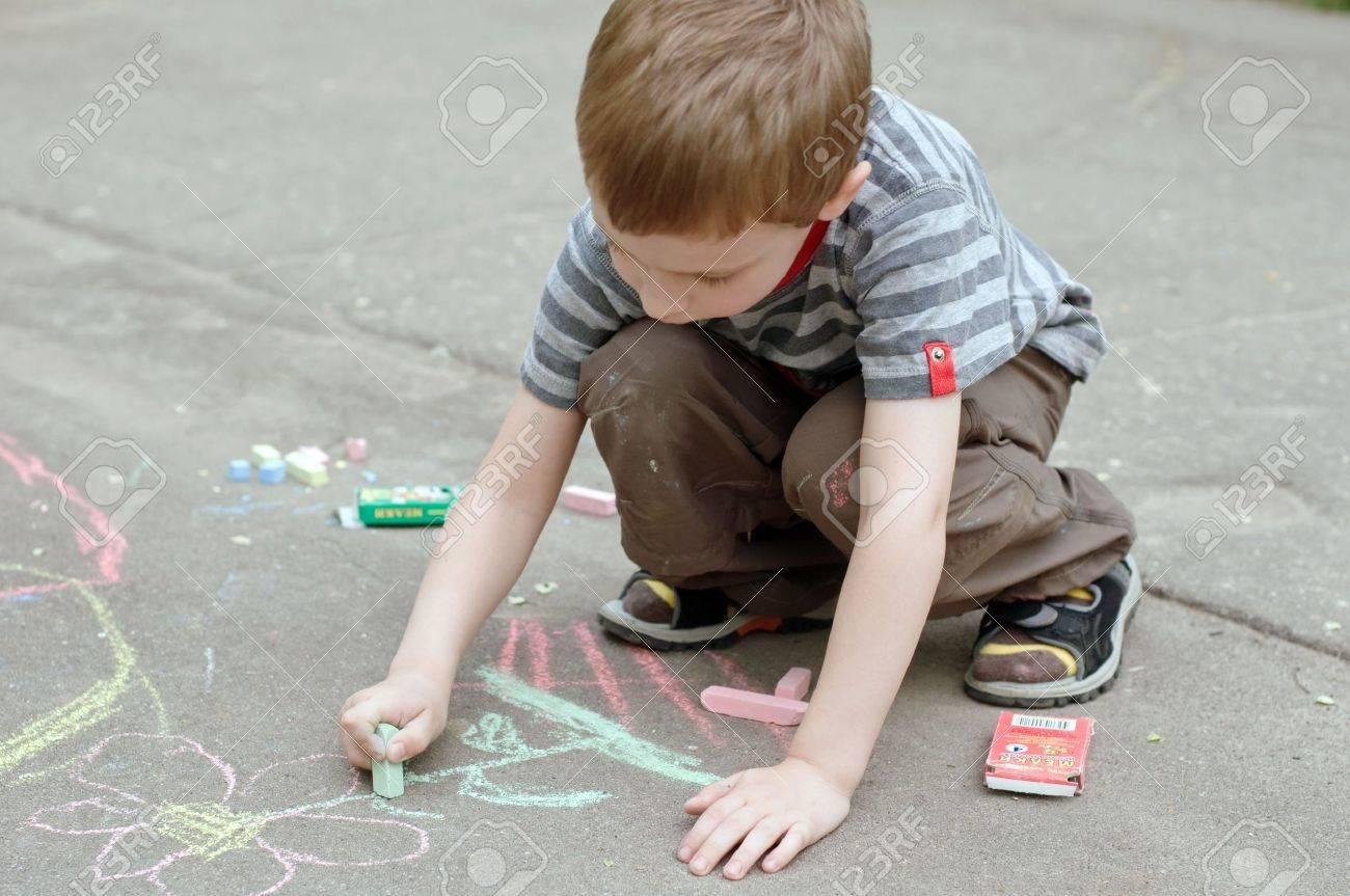 boy drawing with chalk on asphalt Stock Photo - 4980874