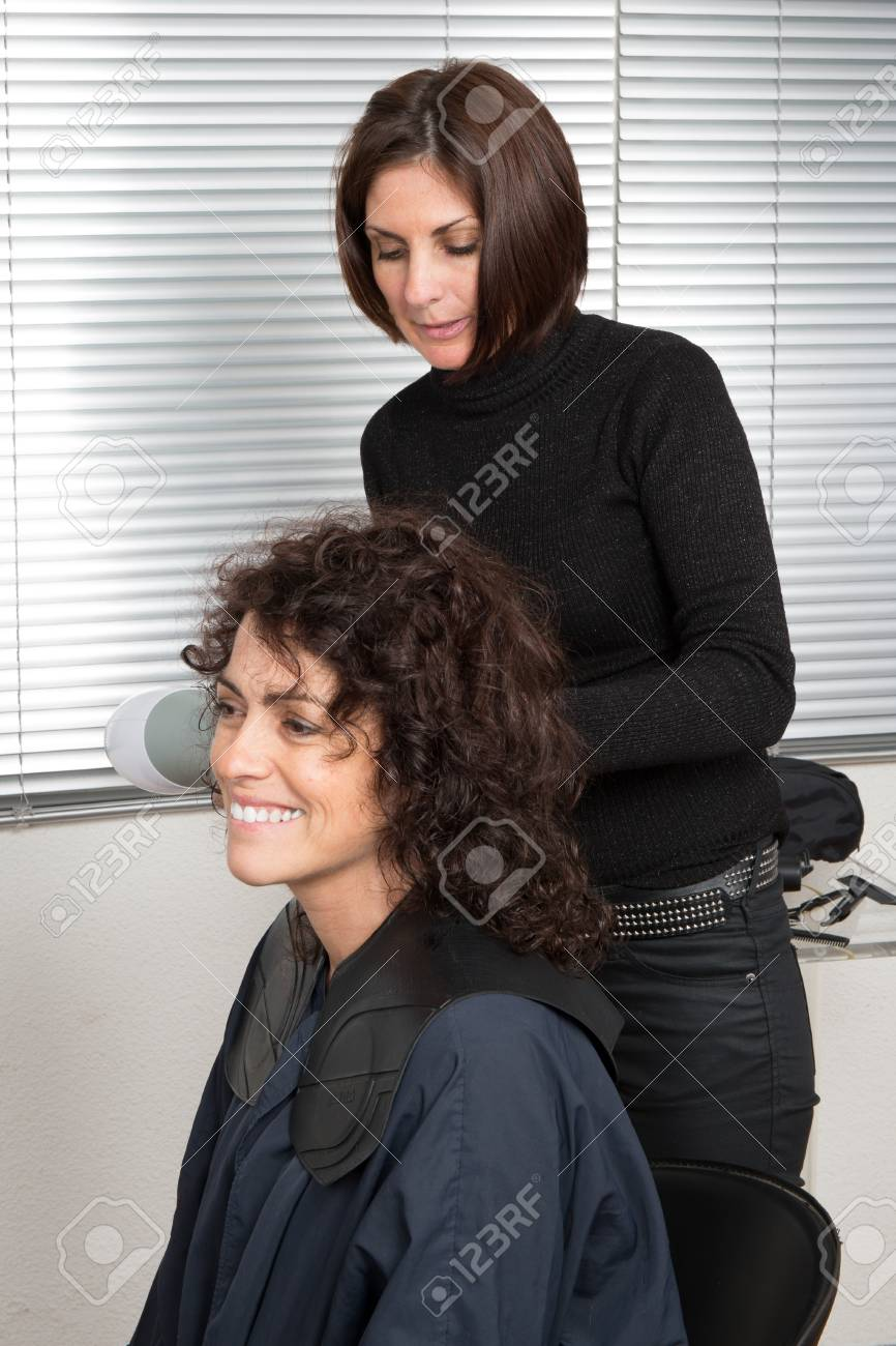 Hairdresser Blow Drying Womans Hair After Giving A New Haircut