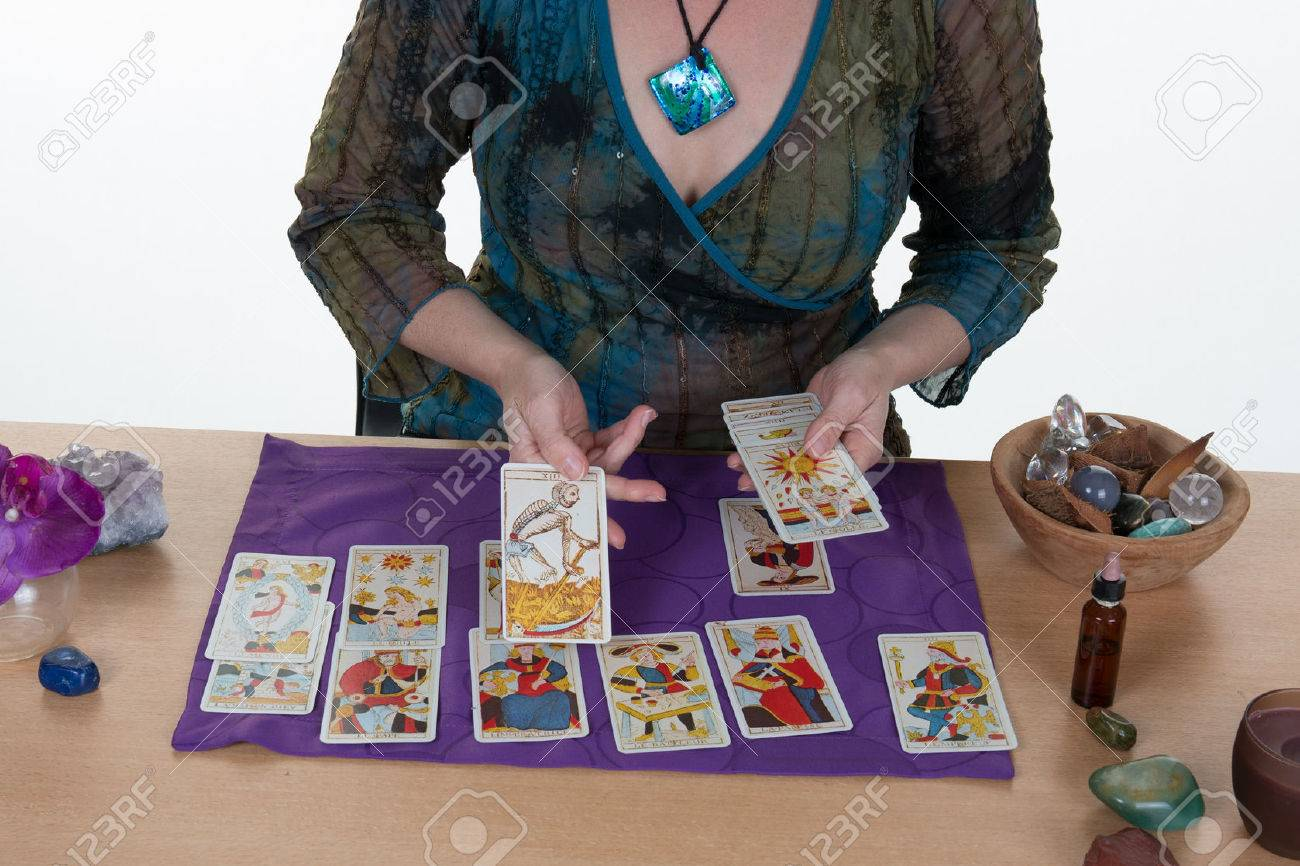 Fortuneteller laying Tarot cards candles are burning - 57712831