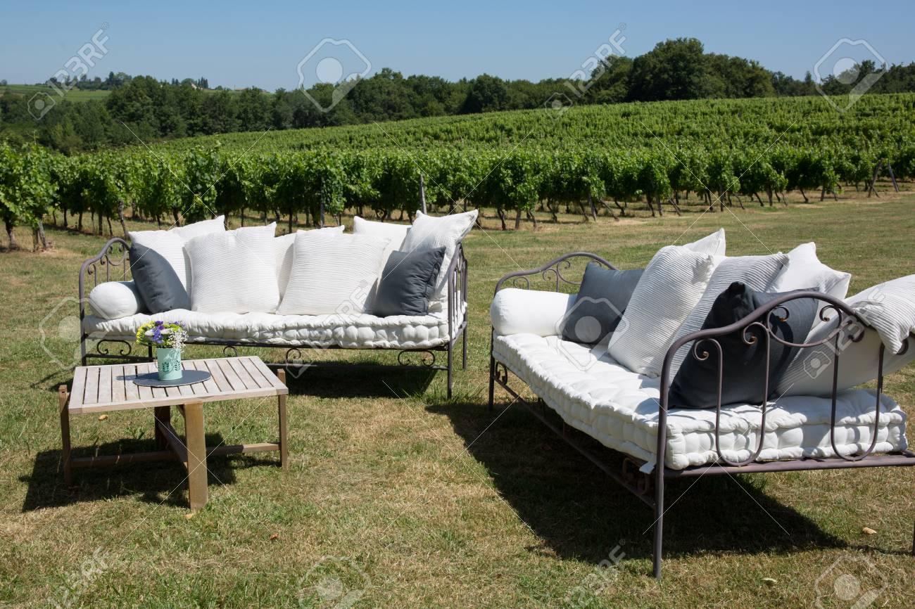 Salon de jardin dans le vignoble avec canapé et table dans l\'herbe