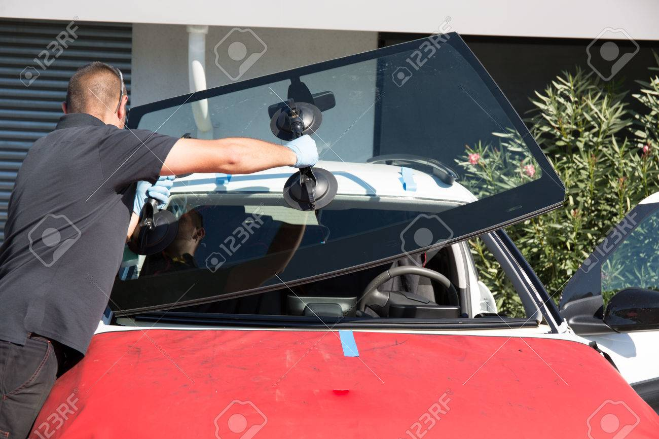 Windshield replacement, man is repairing a windshield - 64336289