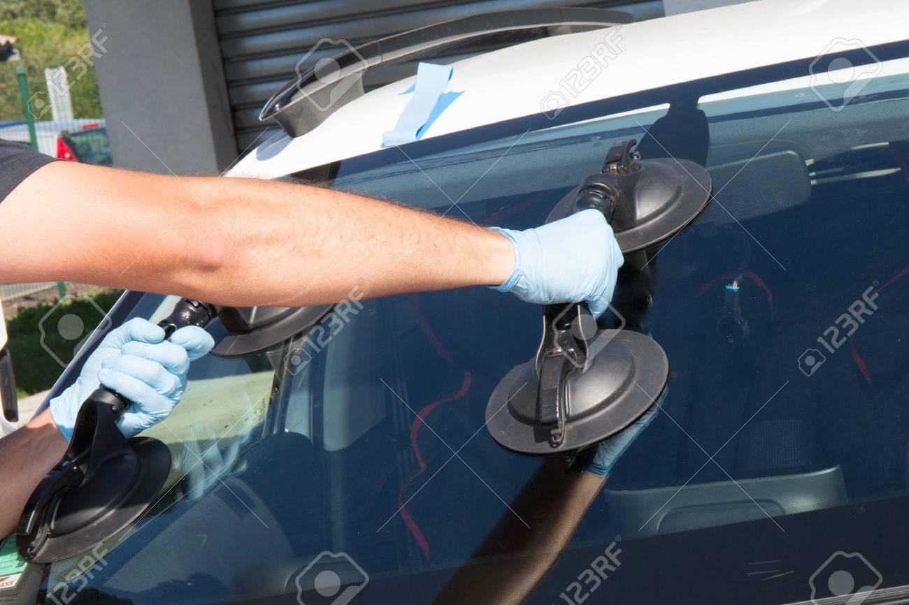Mecanic man is changing windscrenn on a car - 64403758