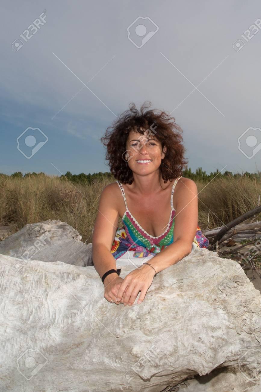baa473a2a Foto de archivo - Vista traseira do retrato de uma mulher sorridente  relaxando em uma praia com um céu azul e mar