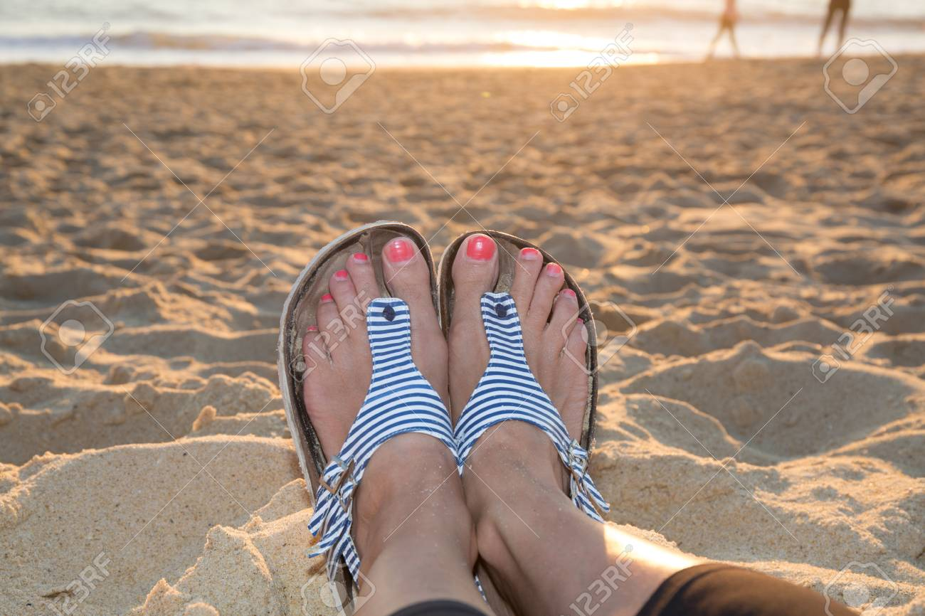 d6d77c5020da4b Seen sea from the beach with the feet of a woman in foreground Stock Photo -