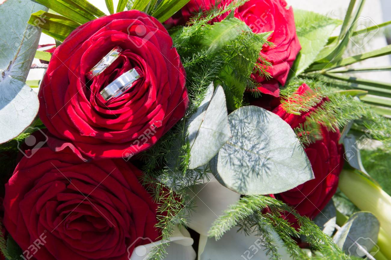 Two Gold Wedding Rings On Red Roses Wedding Bouquet Stock Photo