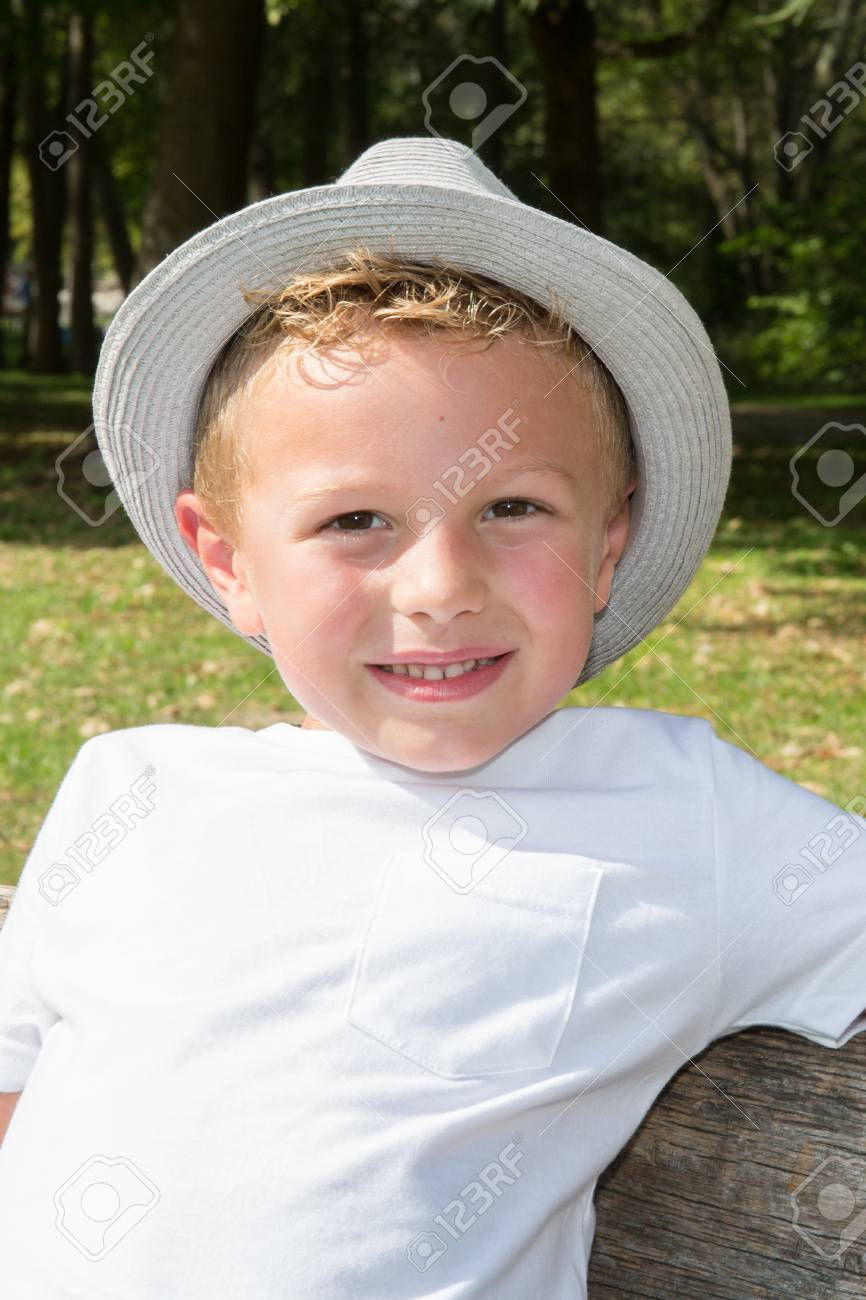 d12c61f8a13 little boy portrait in the park with smile and hat in summer Stock Photo -  87962014