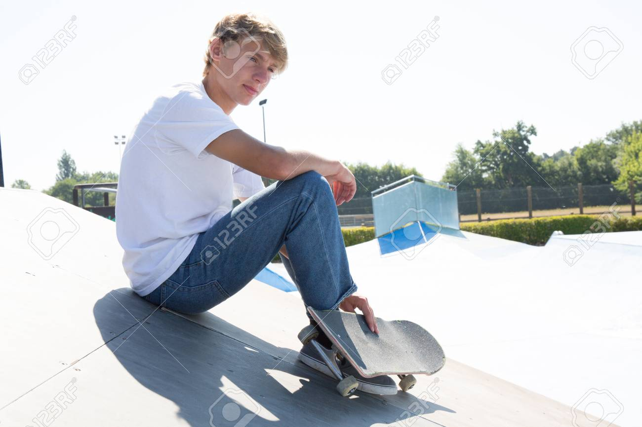 sporty teenager boy sitting on a skate park with his skateboardsporty teenager boy sitting on a skate park with his skateboard, taking a break and