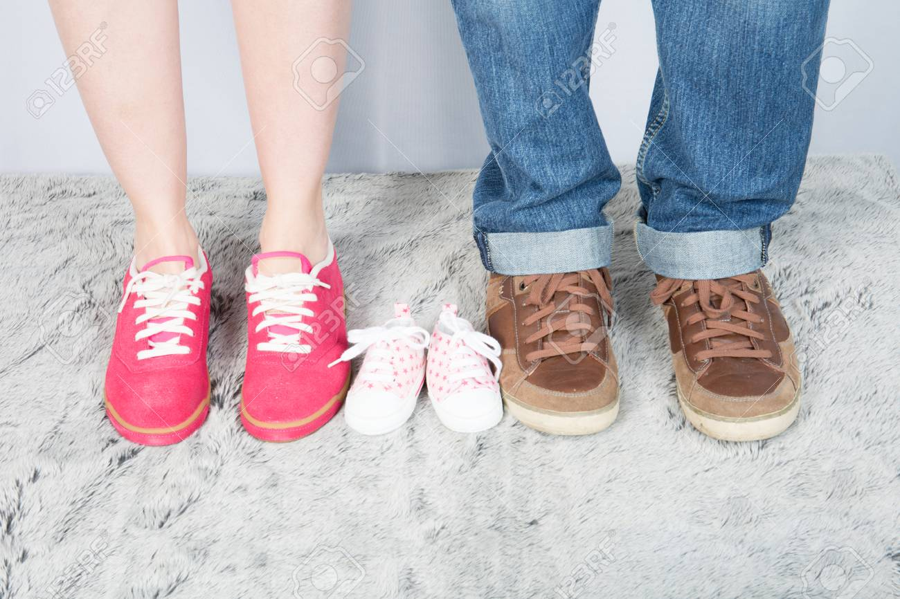 fb7ae69c37827 mother father and baby feet with shoes for family concept foot newborn girl  Stock Photo -