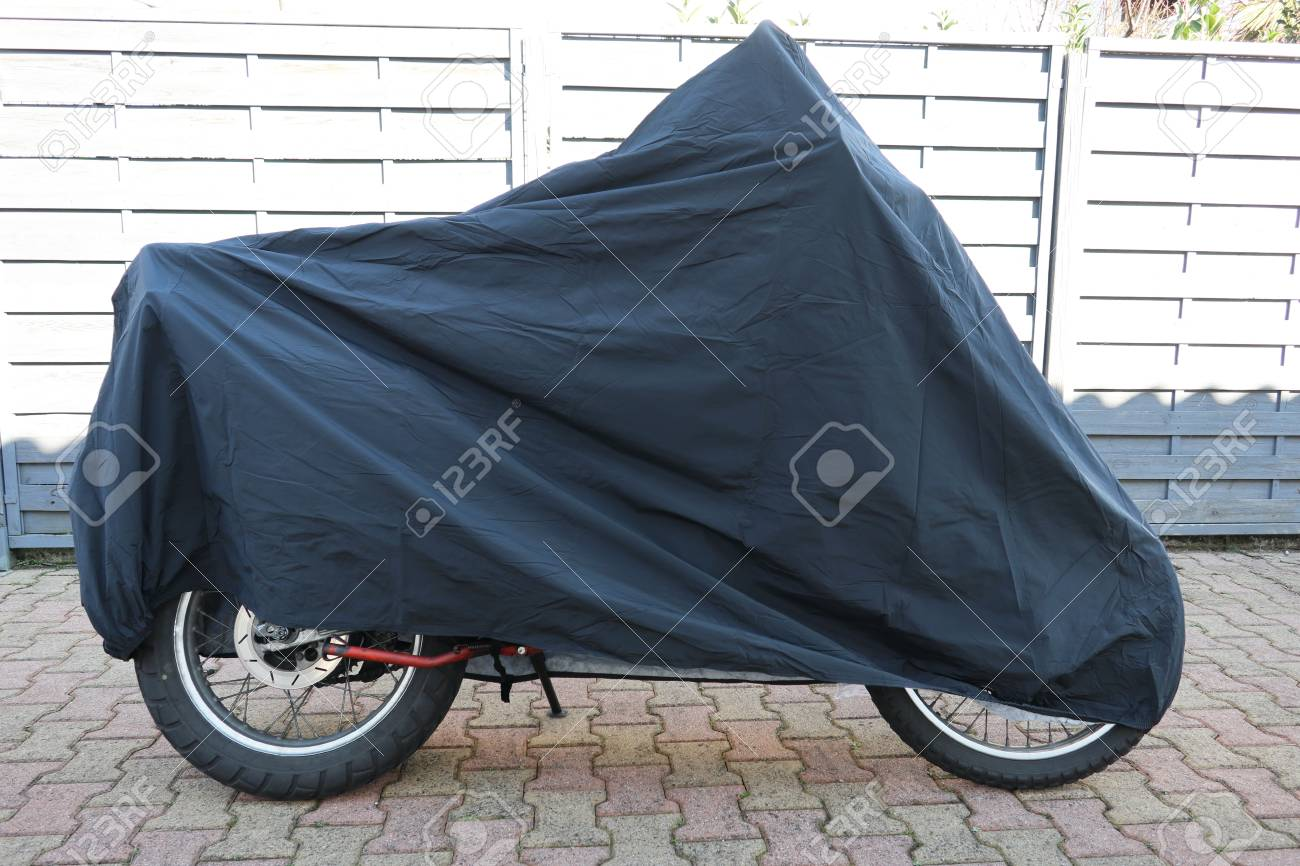 parked motorbike with protective cover in the street - 118428047