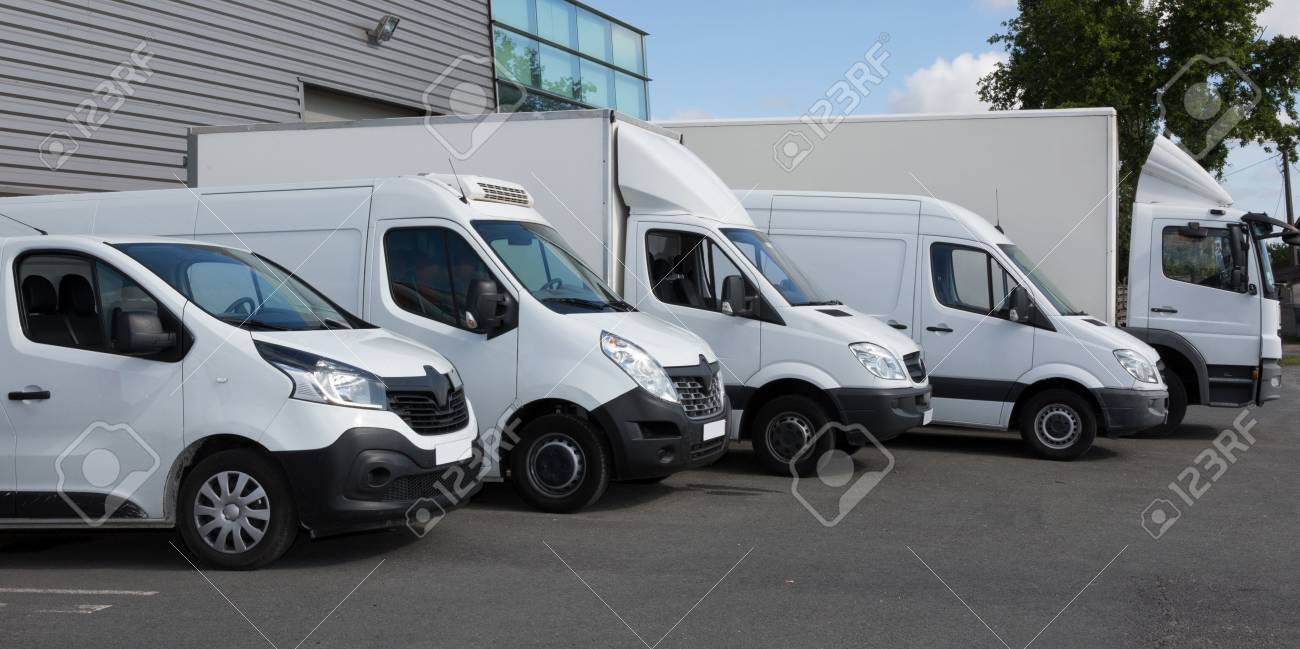 White Delivery Trucks parked in Warehouse Building - 120326312