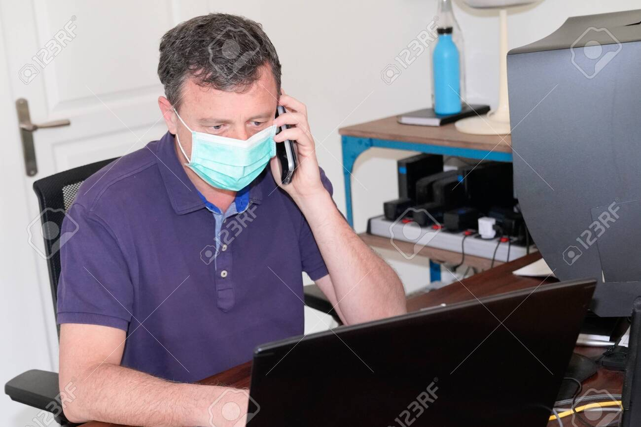 handsome man in protective face mask is talking on phone working computer from home office during Coronavirus COVID-19 virus epidemic quarantine disease - 142889395
