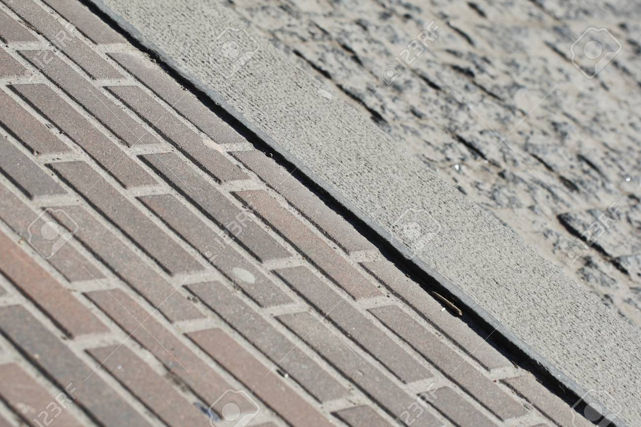 Pavement tiles and a granite curb along the diagonal of the frame