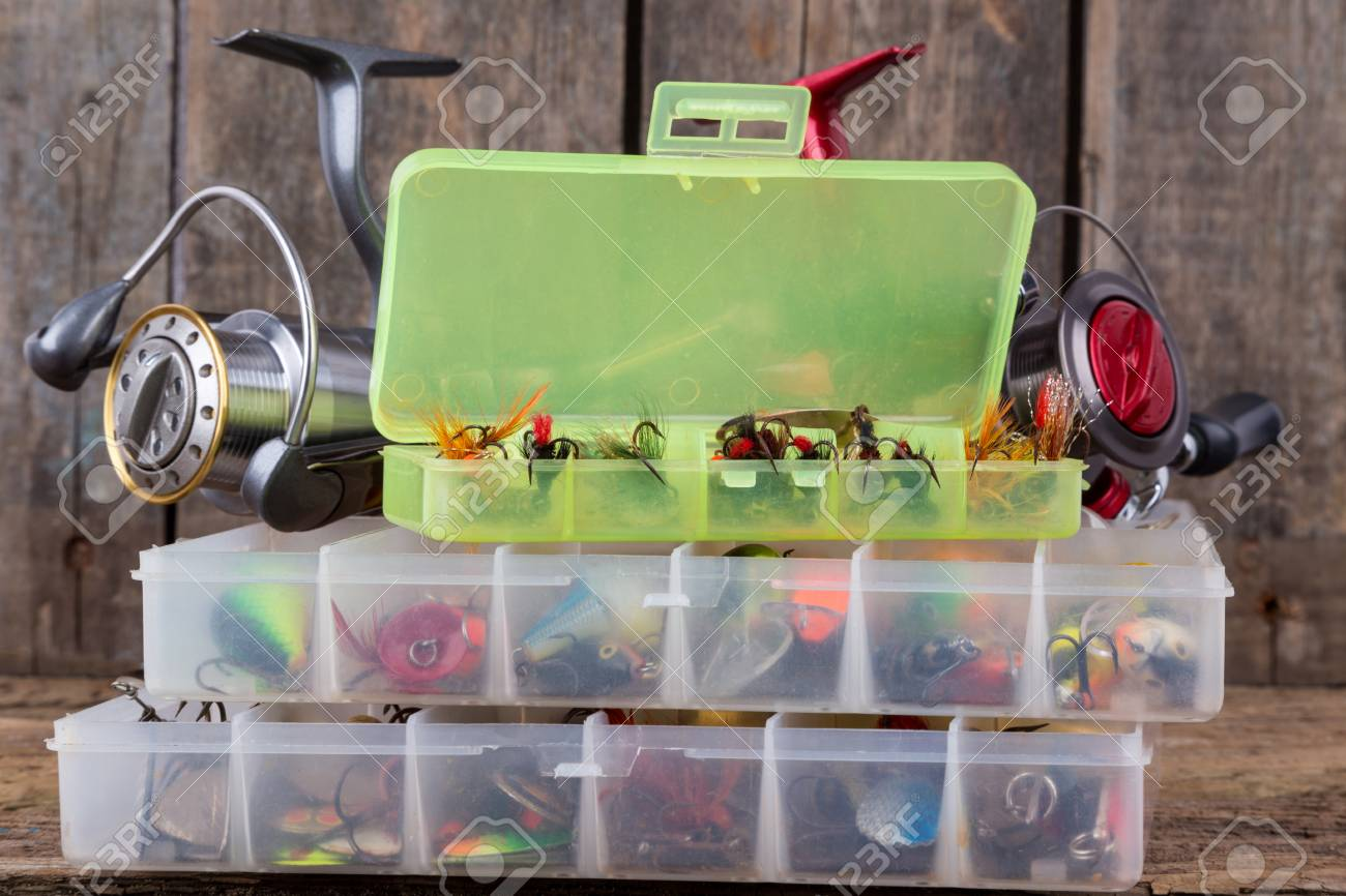 Fishing Tackles And Fishing Baits In Box On Vertical Wooden Board