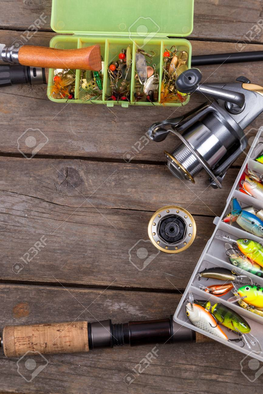Fishing Tackles And Baits In Box On Wooden Board Background Design For Outdoor Sport