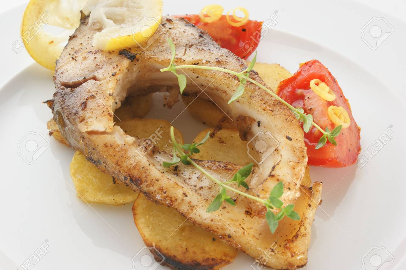 grilled carp fillet on organic potato with lemon Stock Photo - 5399504