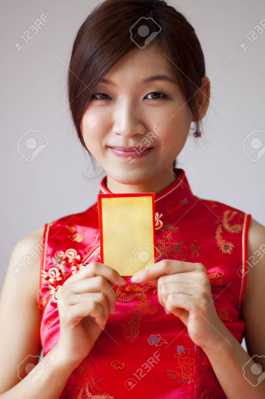Oriental girl in cheongsam wear holding a Chinese red packet wishing you happy Chinese New Year. Stock Photo - 5676258