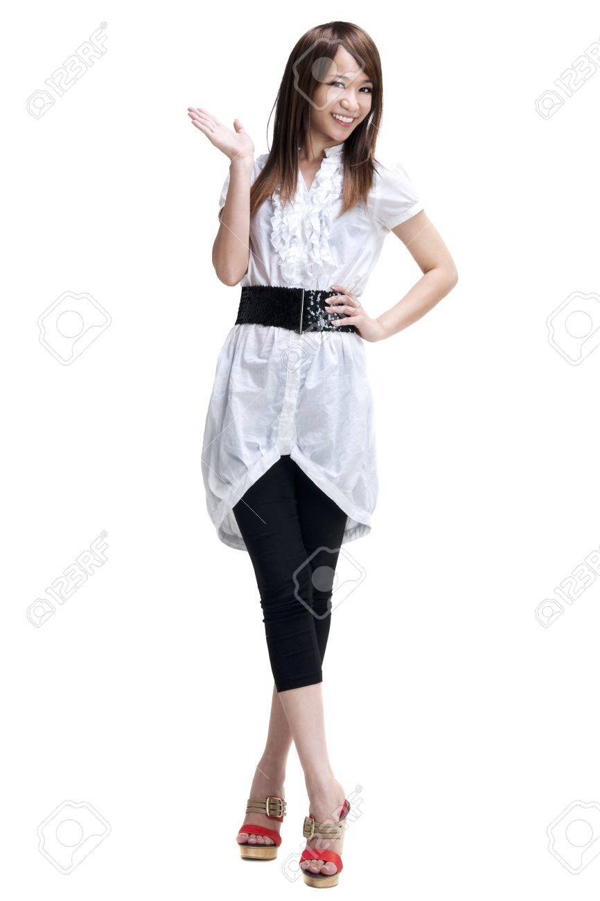 Full length of happy cheerful beautiful Japanese Asian young woman holding her hand out and showing copy space for your product. - 7863303