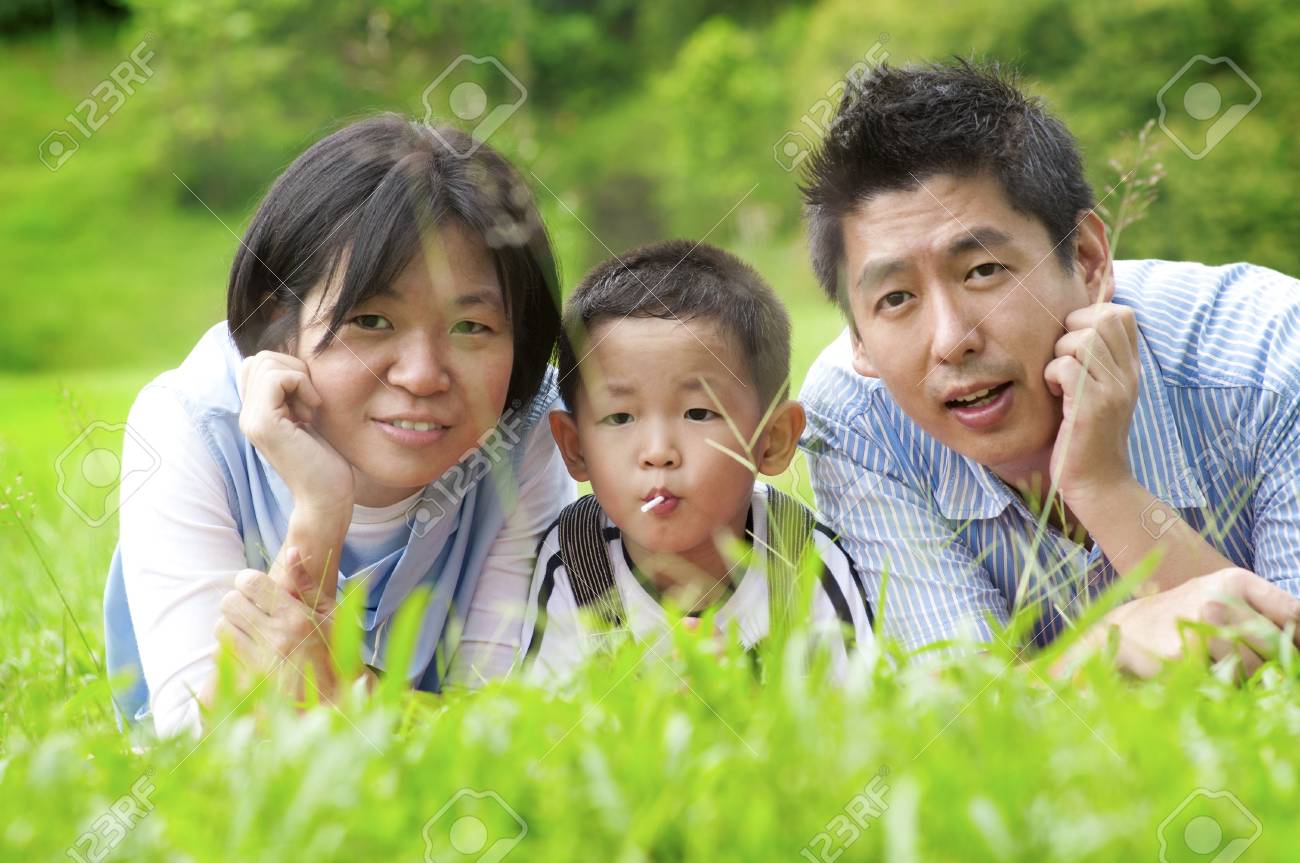 Asian outdoor family lying on green field Stock Photo - 11012261