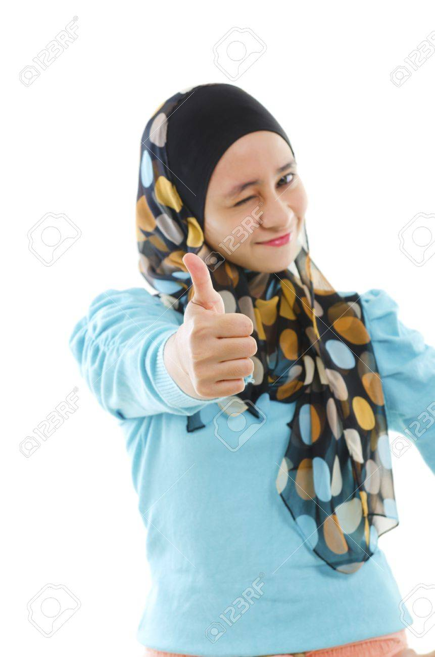 Cute young muslim girl giving a thumb up sign over white background stock photo 14348828
