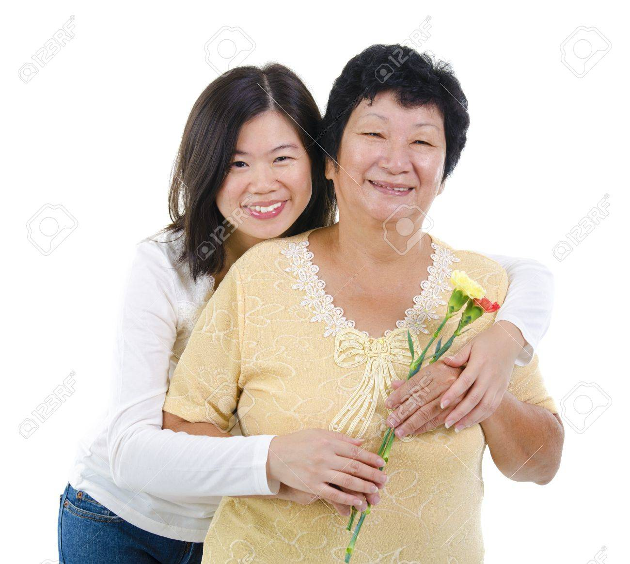 Daughter giving carnation flowers to her mother over white background Stock Photo - 14917211