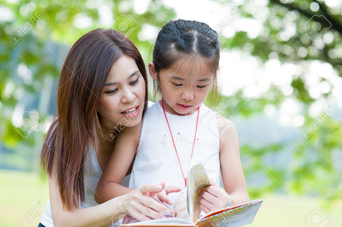 Beautiful little girl reading book with her mother and smiling. Summer park in background. Stock Photo - 16561604
