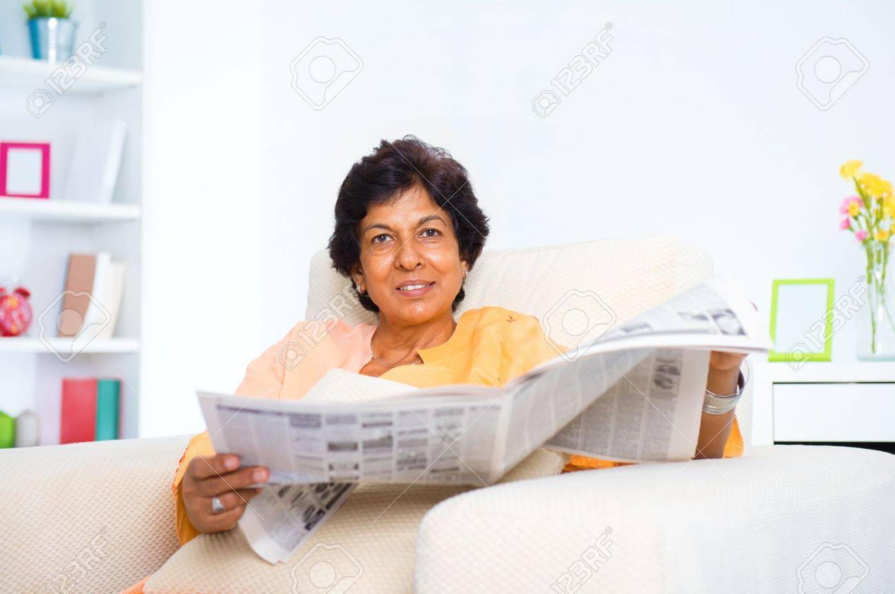Mature 50s Indian woman reading news paper on sofa at home Stock Photo - 16753189