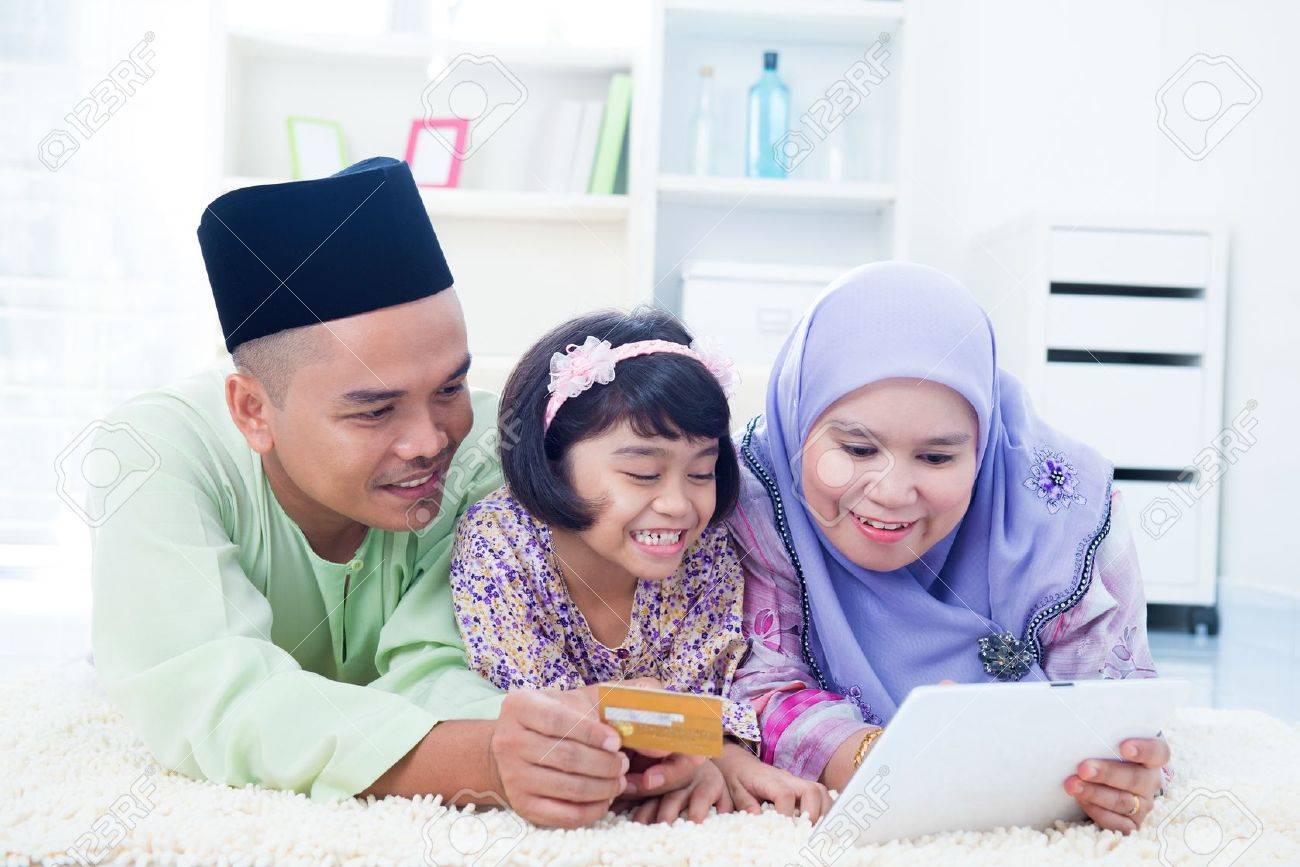 Southeast Asian family online shopping with credit card at home. Muslim family living lifestyle. Stock Photo - 16856843