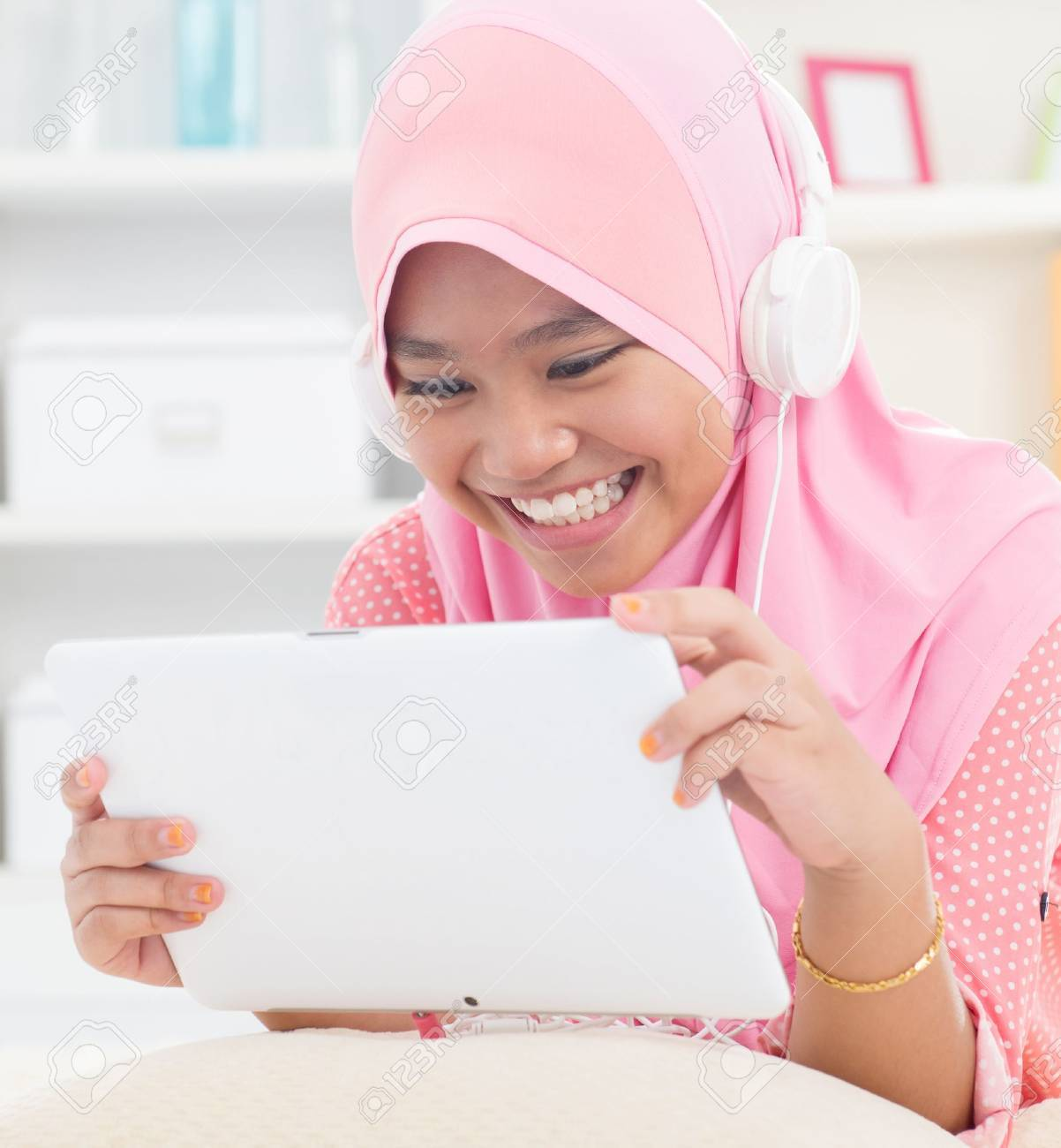 Southeast Asian teenager listen mp3 headphone at home. Muslim teen girl living lifestyle. Stock Photo - 16856834