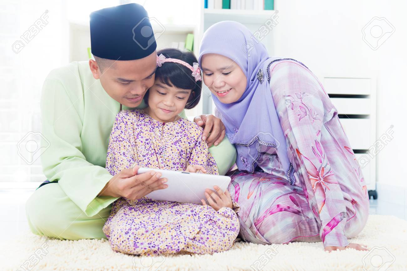Southeast Asian family using computer internet at home. Muslim family living lifestyle Stock Photo - 17056457