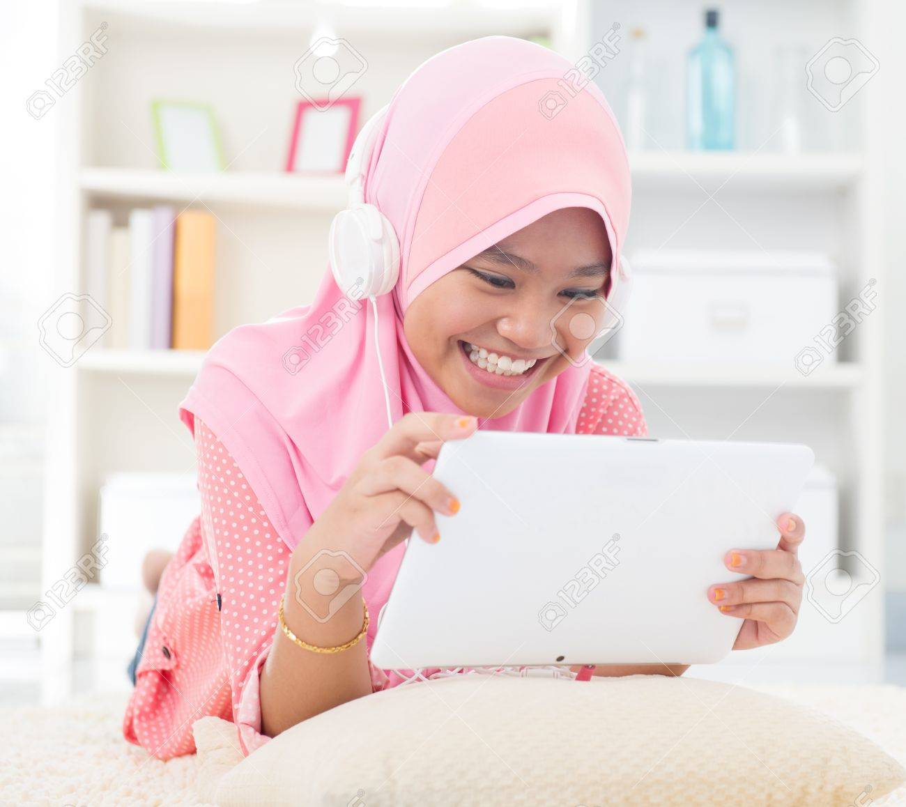 Southeast Asian teenager listen mp3 headphone at home. Muslim teen girl living lifestyle. Stock Photo - 17056487