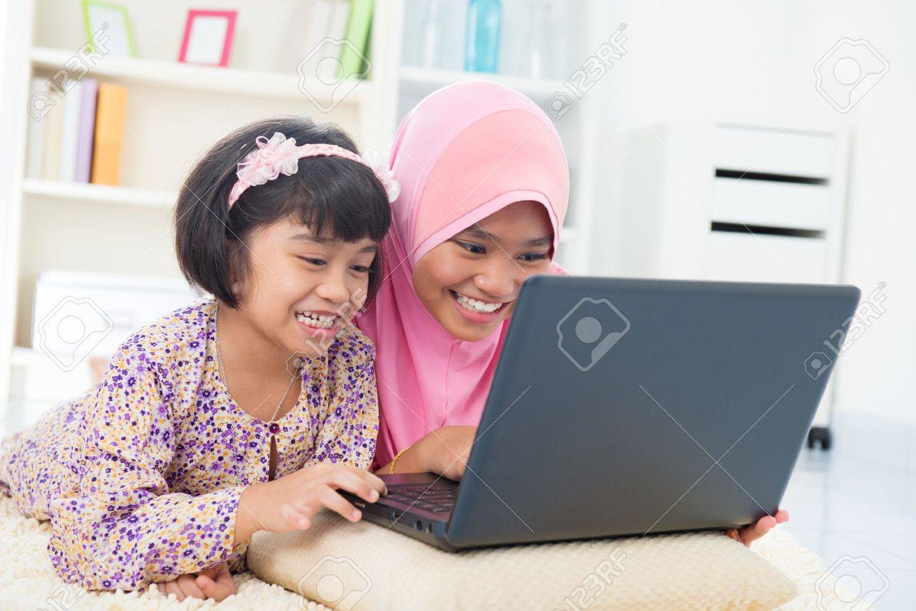 Southeast Asian females surfing internet at home. Malay Muslim girls. Stock Photo - 17056452