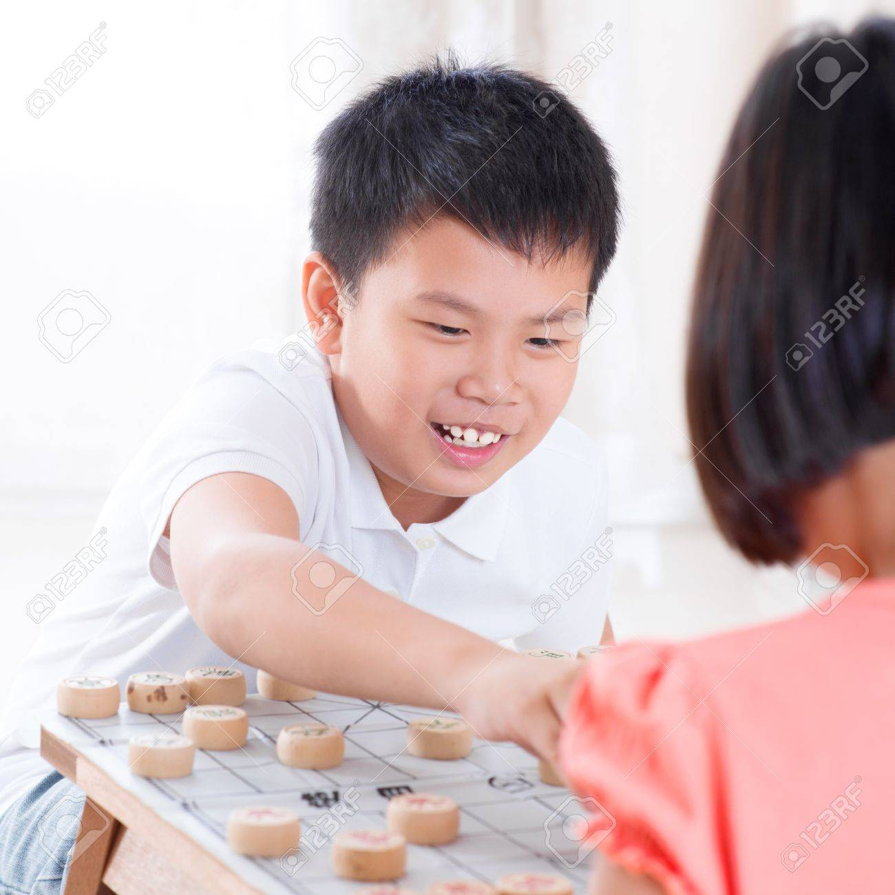 Asian children playing Chinese chess at home. Stock Photo - 18061192